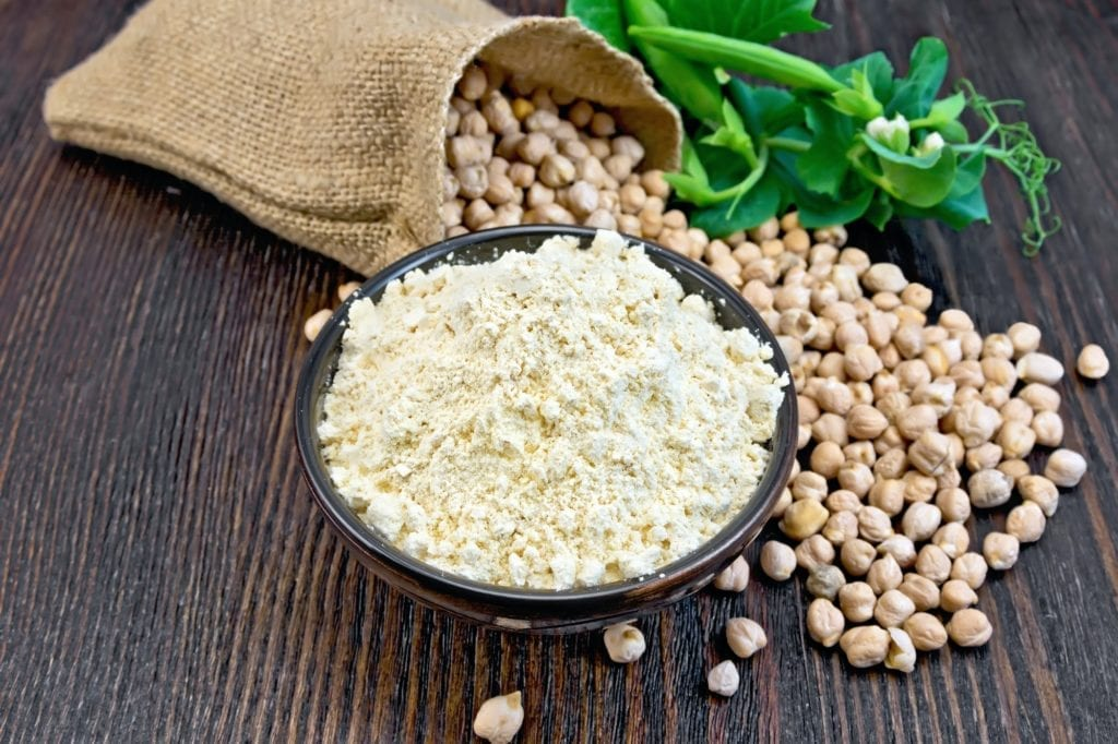 Flour chickpeas in bowl with peas on board