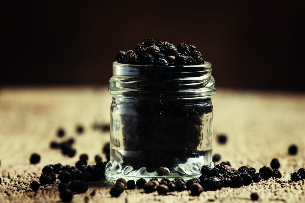 Pea of black pepper in a glass jar